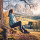 Woman is sitting on the hill under the tree at sunset in autumn - PhotoDune Item for Sale