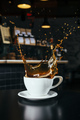 Coffee exploding out of a white cup in a Coffee Shop - PhotoDune Item for Sale