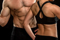 Bodies of male and female fitness model on black background - PhotoDune Item for Sale