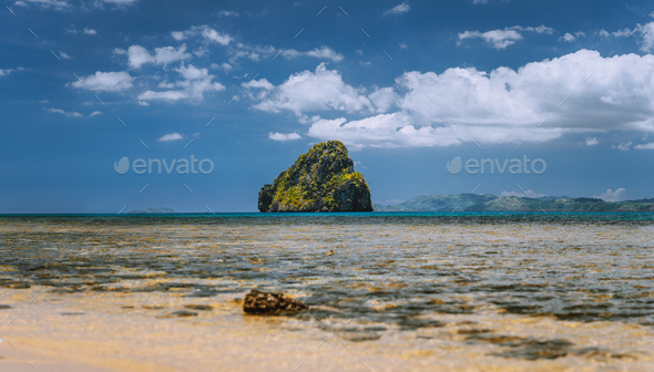 Panoramic low angle shot of beautiful secluded cliff island in open ocean surrounded by turquoise - Stock Photo - Images
