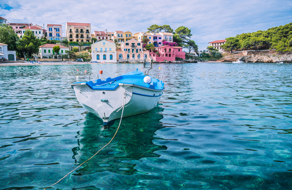 White fishing boat in the blue rippled sea water bay in Assos village, Kefalonia island, Greece - Stock Photo - Images