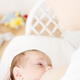 Young happy smiling mom breastfeeding her little baby boy. - PhotoDune Item for Sale