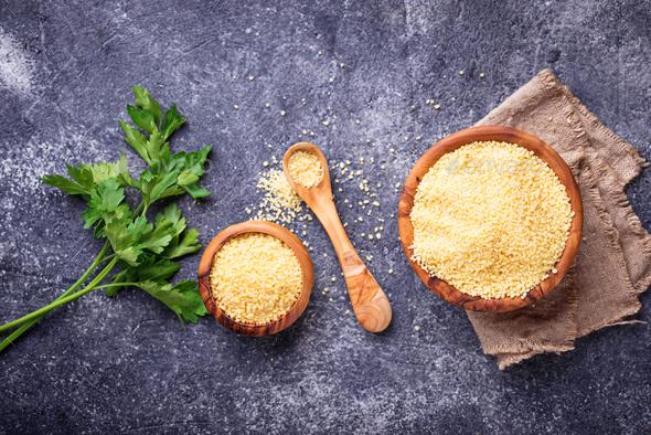 Couscous grain in wooden bowl - Stock Photo - Images