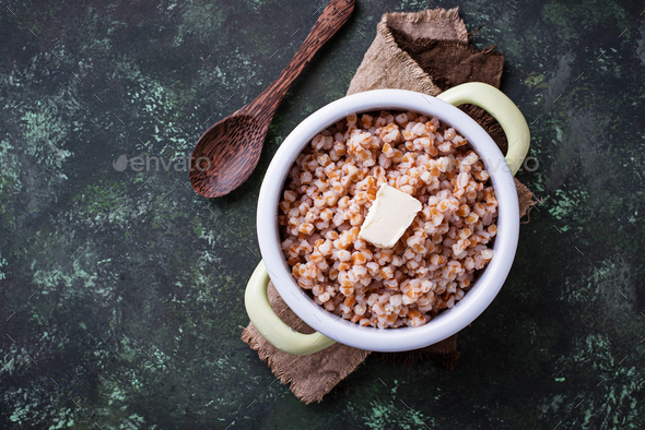 Barley porridge with butter in green pot - Stock Photo - Images