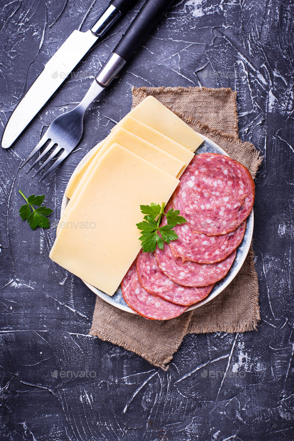Sliced cheese and salami on plate - Stock Photo - Images