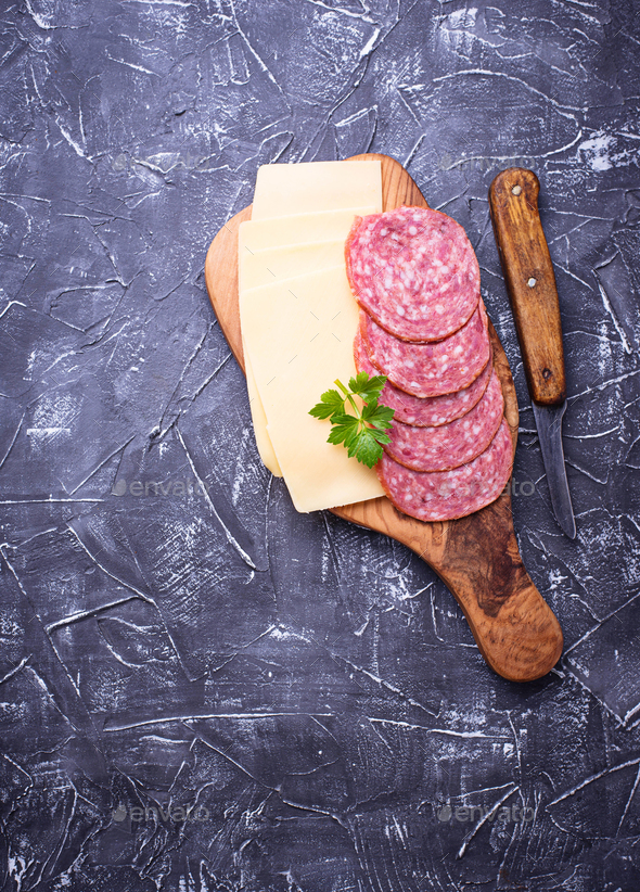 Sliced cheese and salami on wooden board - Stock Photo - Images