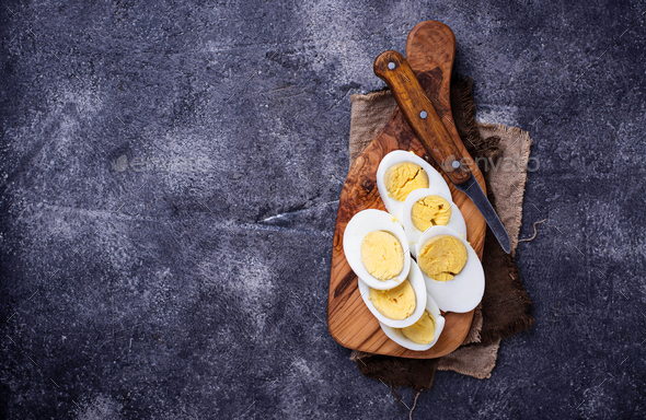 Boiled sliced chicken eggs on cutting board - Stock Photo - Images