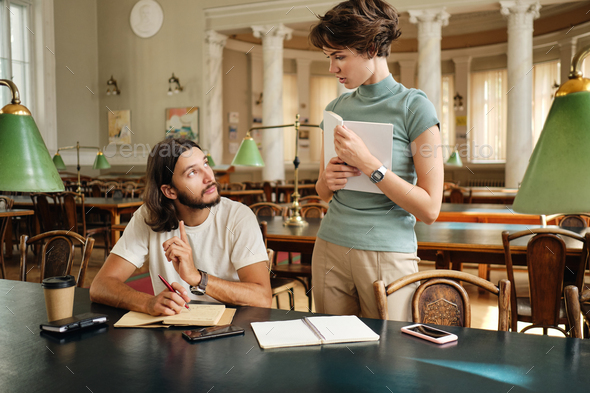 Attractive tutor girl discussing with student guy new topic during lesson in university library - Stock Photo - Images