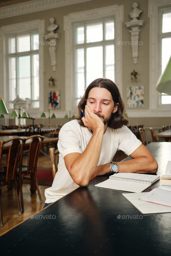 Young wistful male student thoughtfully leaning on hand studying in library of university - Stock Photo - Images