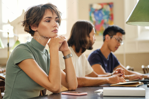 Portrait of pensive girl tiredly studying with students in library of university - Stock Photo - Images