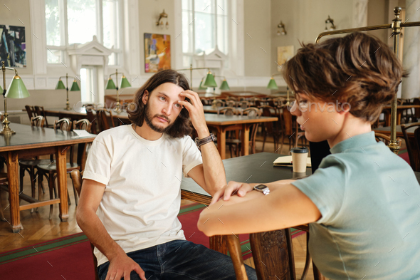 Young casual male student thoughtfully taking verbal exam to teacher in lecture room of university - Stock Photo - Images
