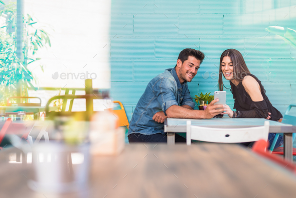 Happy young couple seating in a restaurant with a smartphone - Stock Photo - Images