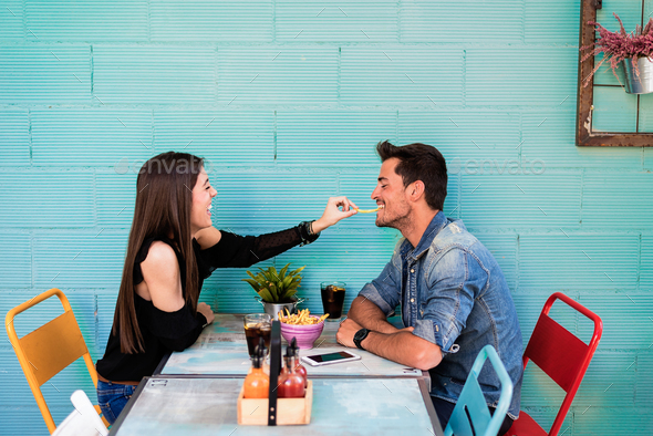 Happy young couple seating in a restaurant - Stock Photo - Images