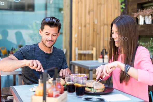 Happy young couple seating in a restaurant terrace eating a burg - Stock Photo - Images