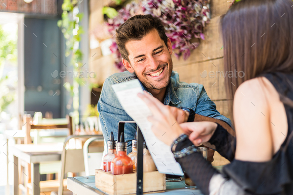 Happy young couple seating in a restaurant looking at the menu - Stock Photo - Images