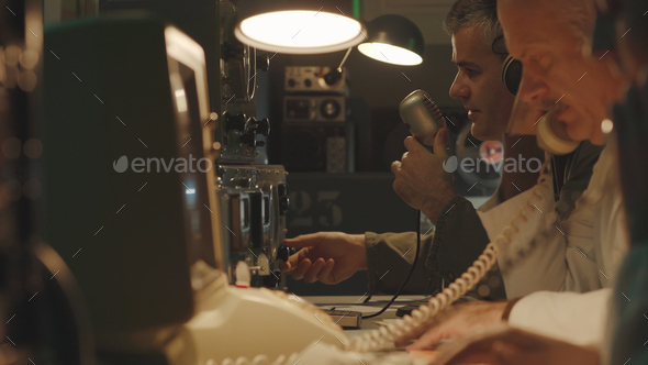 Scientists working in a vintage control room - Stock Photo - Images