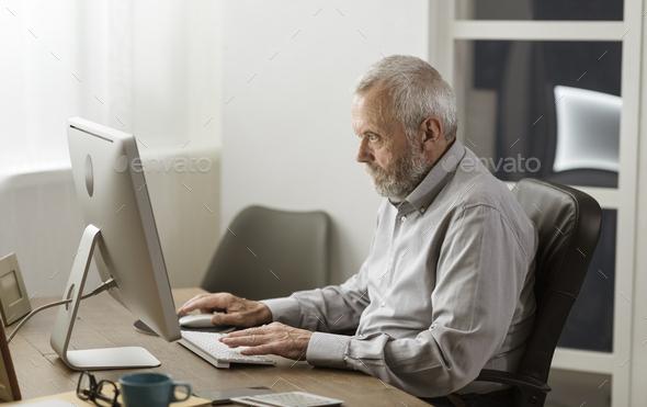 Senior man using his computer at home - Stock Photo - Images