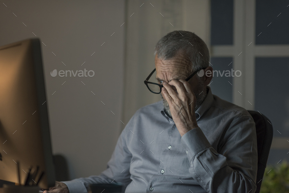 Senior man working with his computer at night - Stock Photo - Images