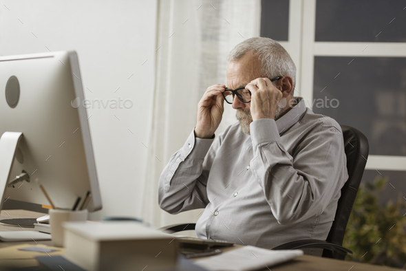 Senior man adjusting his glasses and working with his computer - Stock Photo - Images