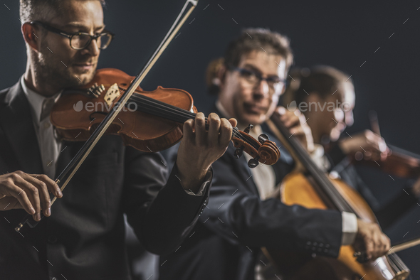 Symphonic string orchestra performing on stage - Stock Photo - Images