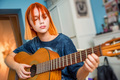 Pretty red-haired teenage girl plays guitar in her room - PhotoDune Item for Sale