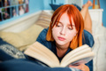 Pretty red-haired teenage girl reads book in her room - PhotoDune Item for Sale