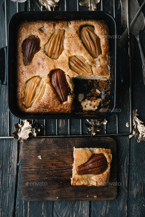 Fall french pear cake in a black ceramic bakeware - Stock Photo - Images