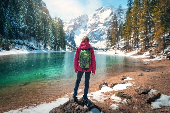 Woman with backpack on the stone near lake with azure water - Stock Photo - Images
