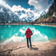 Young woman in red jacket is standing near lake with azure water - PhotoDune Item for Sale