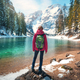 Woman with backpack on the stone near lake with azure water - PhotoDune Item for Sale
