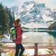 Woman with backpack near lake with azure water in autumn - PhotoDune Item for Sale