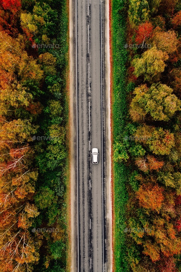 Aerial view of road and a car in autumn forest with red, yellow and orange leaves. - Stock Photo - Images