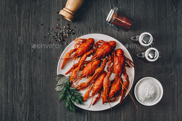 Boiled big red fresh crawfish in white plate with green herbs - Stock Photo - Images
