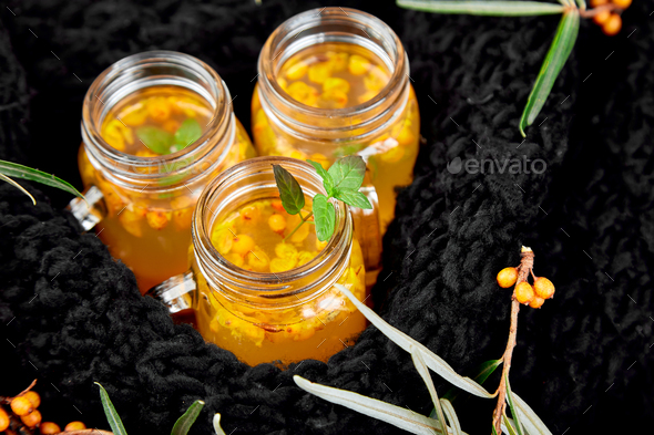 Hot sea buckthorn tea with black warm scarf - Stock Photo - Images