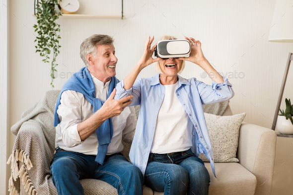 Mature woman testing VR glasses with husband - Stock Photo - Images