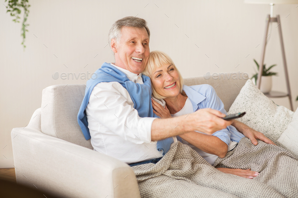Relaxed senior couple watching television at home - Stock Photo - Images