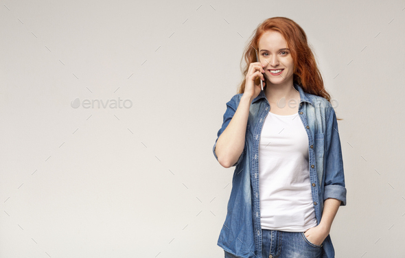 Girl talking on mobile phone, smiling and looking to camera - Stock Photo - Images