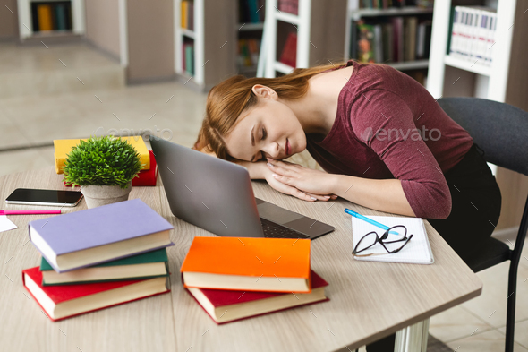 Exhausted girl having nap on workplace in front of laptop - Stock Photo - Images