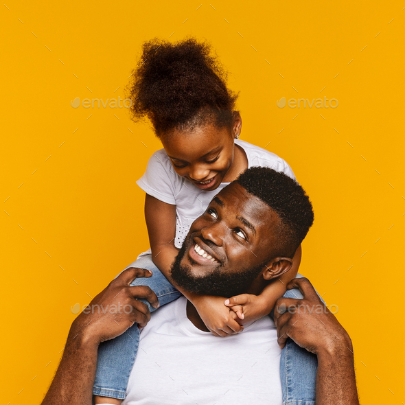Cute african american little girl sitting on her daddy's shoulders - Stock Photo - Images