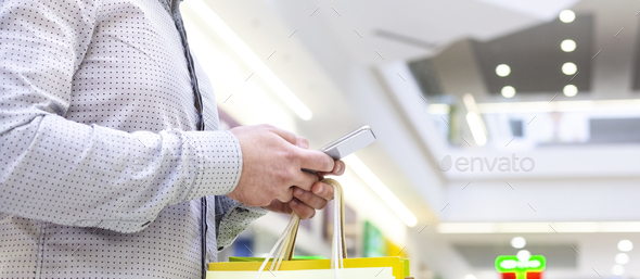 Man shopping in mall and using phone, copy space - Stock Photo - Images