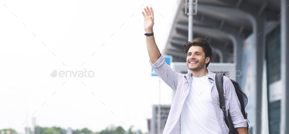 Young man waving hand near airport building, panorama - Stock Photo - Images