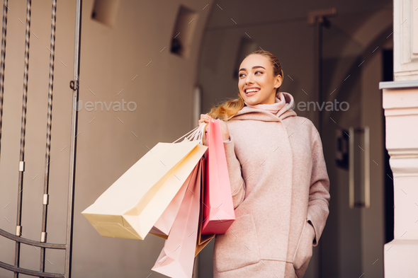 Shopaholic woman with shopping bags, walking in the city - Stock Photo - Images