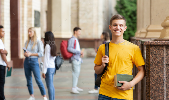 College student smiling to camera, standing against friends - Stock Photo - Images