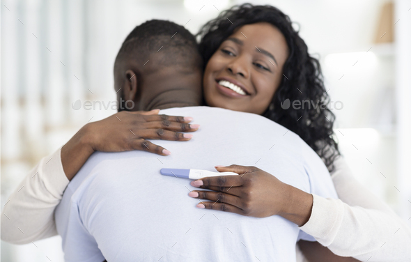 Couple Happy About Pregnancy Test Result, Hugging Each Other - Stock Photo - Images