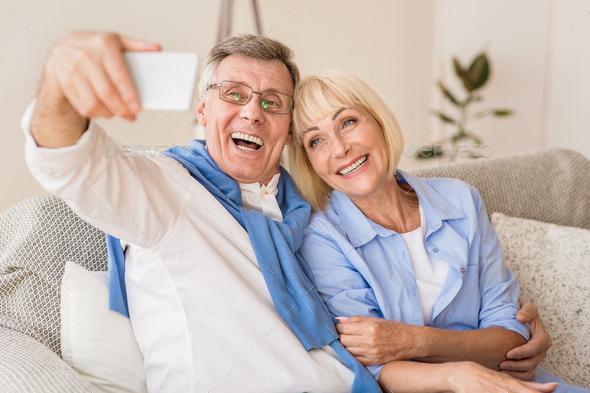 Modern grandparents taking selfie on cellphone, resting on sofa - Stock Photo - Images