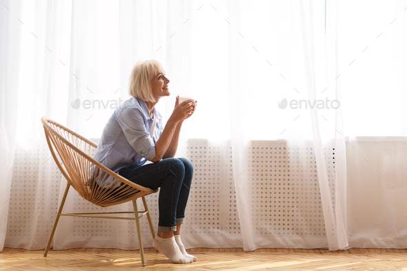 Senior woman sitting on chair in front of window and drinking tea - Stock Photo - Images