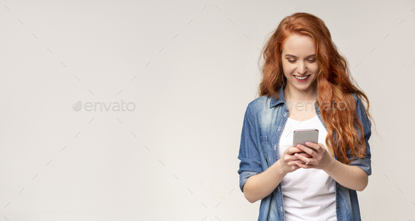 Cool Application. Curious Girl Using Smartphone On Light Background - Stock Photo - Images
