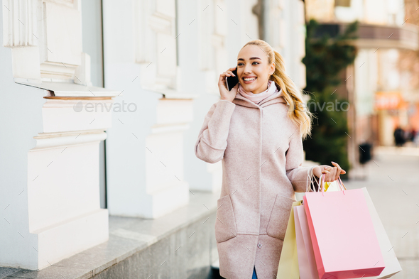 Young woman enjoying walk after shopping in city center - Stock Photo - Images