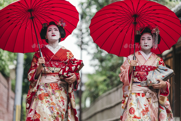 Maiko geishas walking on a street of Gion - Stock Photo - Images