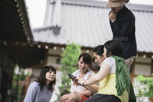 Group of japanese tourists using a tablet - Stock Photo - Images